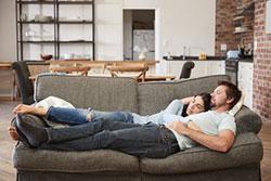 Paar liegt entspannt auf der Couch