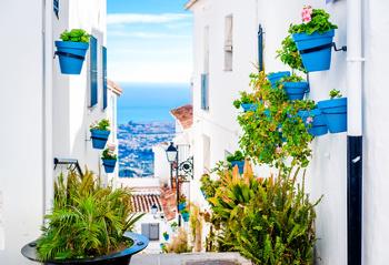 Eine weiße Häusergasse mit blauen Blumentöpfen in Südeuropa