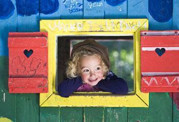 Kleines Mädchen kuckt aus dem Fenster eines bunt bemalten Spielhauses